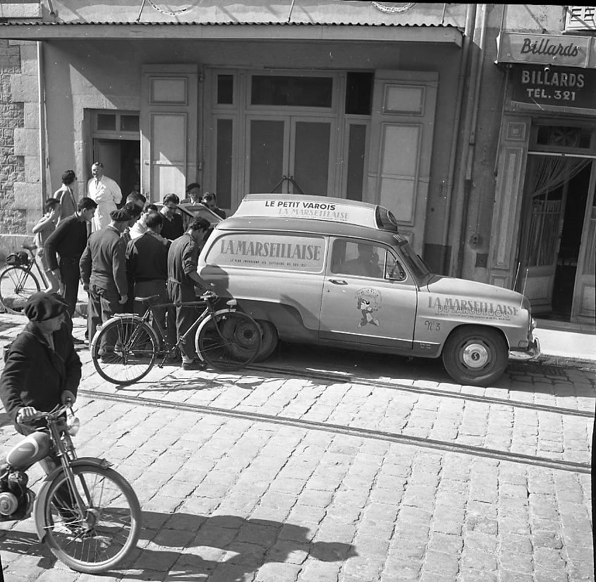 27 Fi 1318 - 32.A leur sortie, les ouvriers des CNC s'empressent vers le coffre de la voiture publicitaire de La Marseillaise pour obtenir leur quotidien. - 12/10/1956