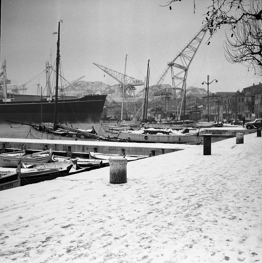 27 Fi 1642 - 2.L'hiver 56 qui a frappé la France, n'épargnera pas La Ciotat, comme le montre cette vue atypique du Vieux Port totalement figé et des Trois Secs enneigés. - 10/02/1956