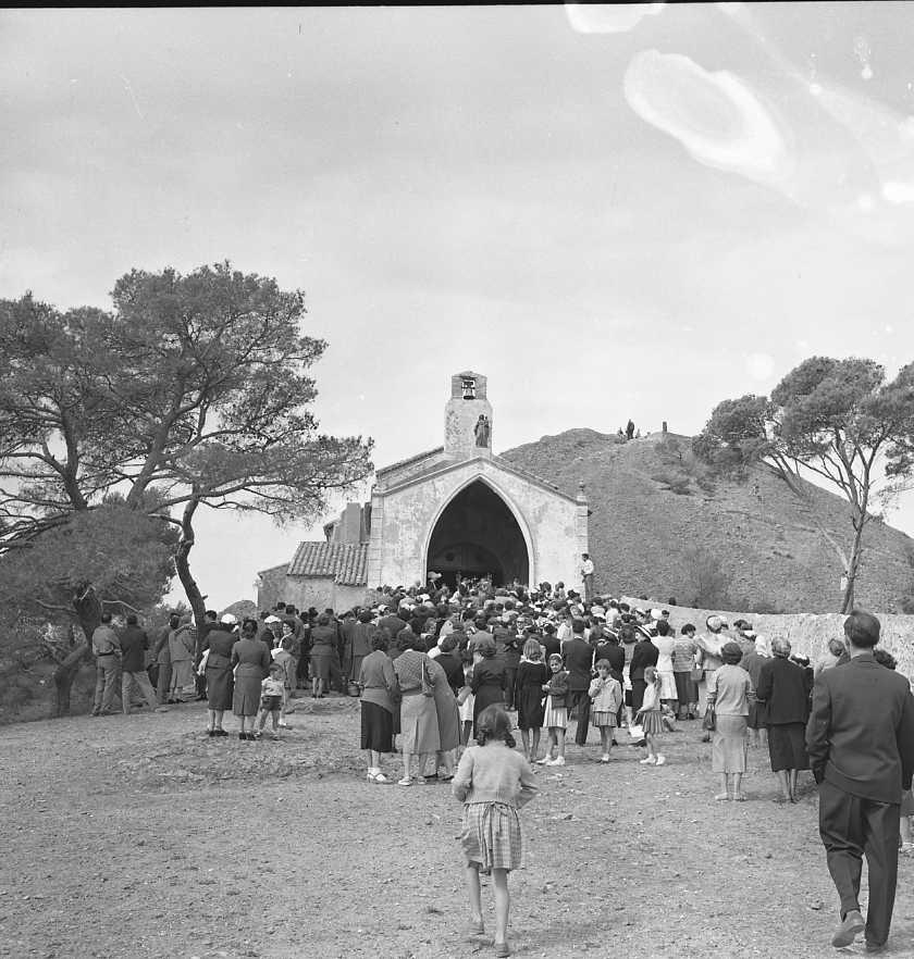27 Fi 2621 - 14.Rassemblement des familles sur le parvis de la Chapelle Notre Dame de La Garde pour la célébration des communions. Aujourd'hui les grands pins ont disparu. - 18/05/1956