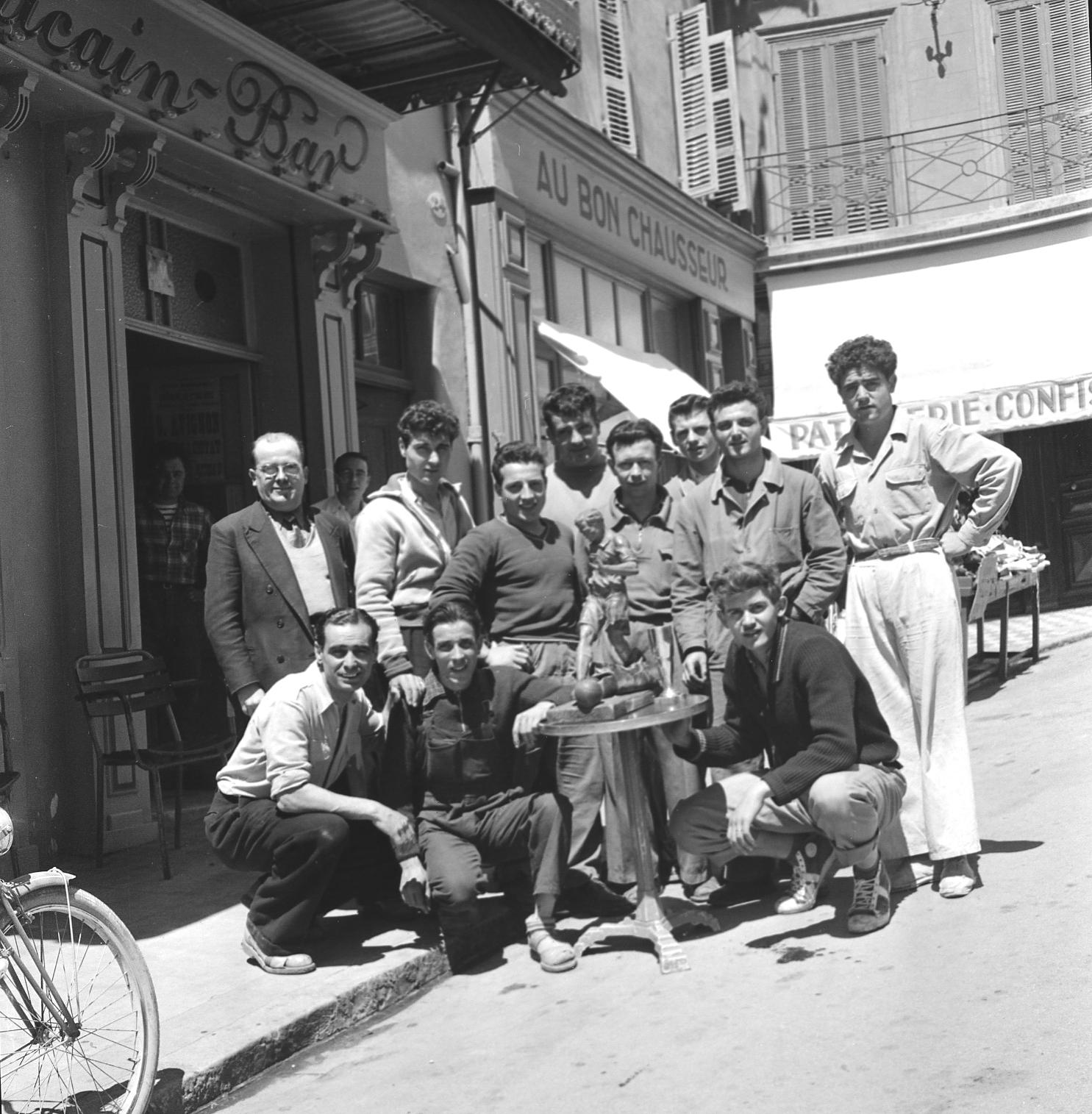 27Fi 1744 - Des footballeurs posant fièrement devant la coupe remportée lors du challenge de St Cyr/Mer, devant le bar américain nouvellement transformé en laverie. 7/05/1953