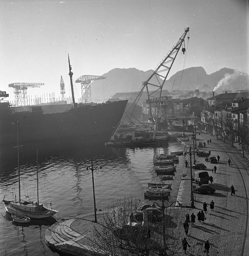 27 Fi 366 Ambiance habituelle à l'Escalet : des promeneurs sur les pavés, quelques véhicules faisant face aux pointus, et en fond le Laos et le ponton mâture amarrés au quai d'armement. 15/01/1953