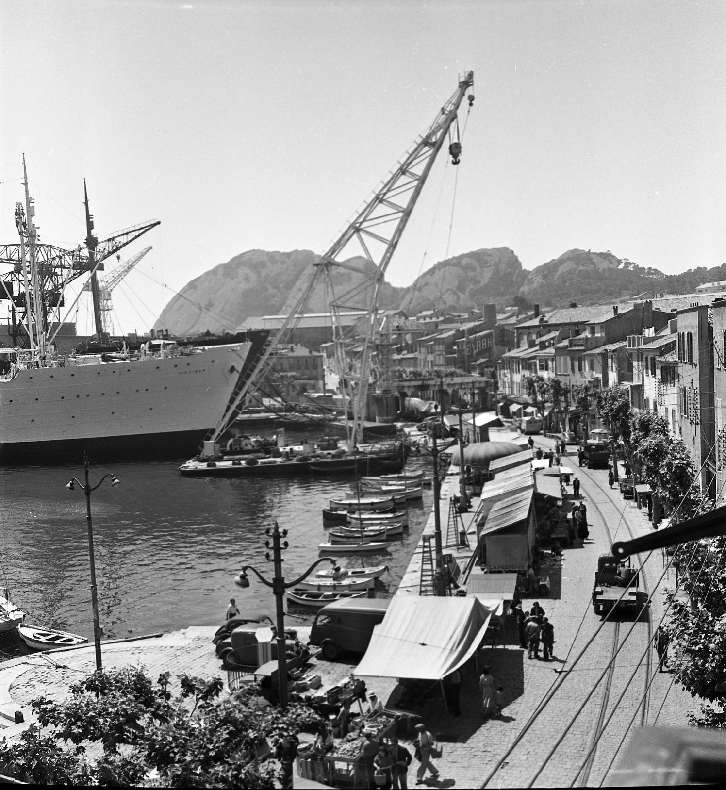 Ce jeudi 21 mai 1953, des forains sont installés le long des quais. Les stands semblent minuscules au regard du paquebot Viêt-Nam et du ponton mature.