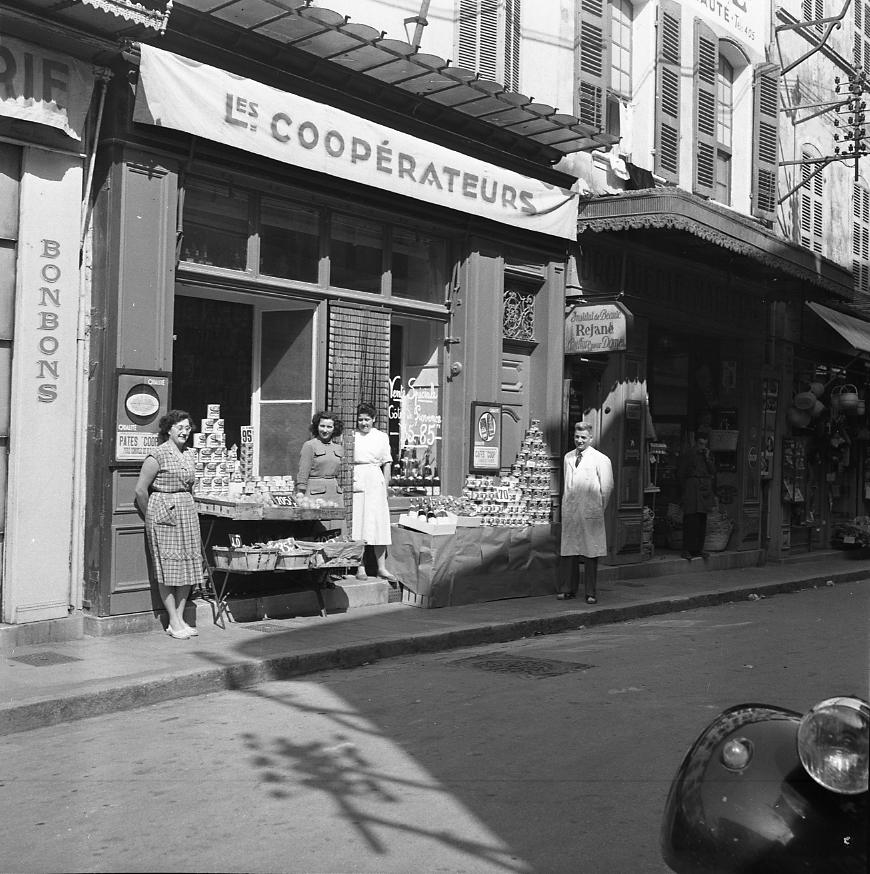 44Fi 1782 - Le gérant M. Frandon et les employés de la coopérative, rue François Donzel, posant devant leur étal bien fourni. 10/05/1954