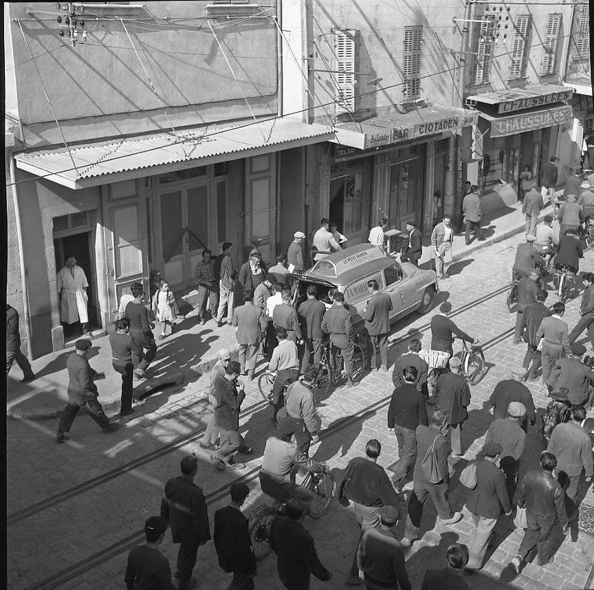 Profitant de ce flux continu d'ouvriers sortant du travail, le marchand de journaux « La Marseillaise » et « Le Petit Varois » fait le plein. - 12/10/1956