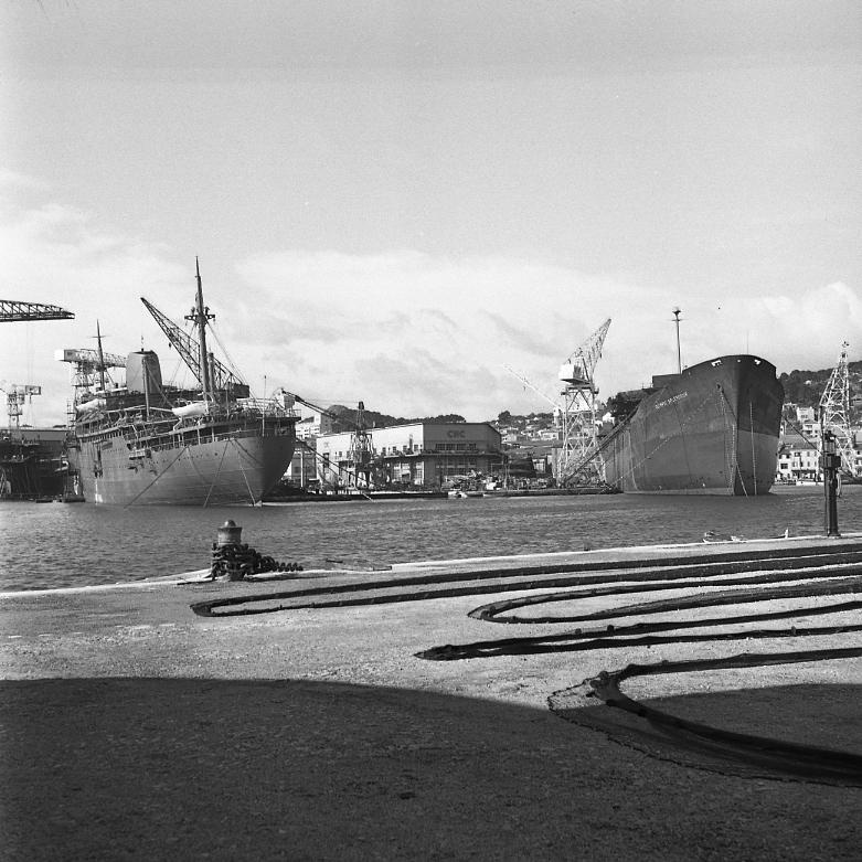 44 Fi 178 Contraste entre la finesse des filets de pêche séchant sur les quais et la masse importante du Laos et de l'Olympic Splendour en cours d'achèvement autour du bâtiment d'armement. A droite la pompe à essence attend les pêcheurs. 2/03/1954
