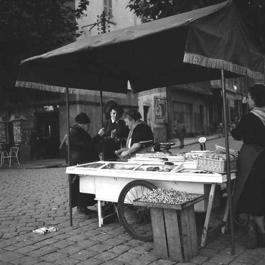 27Fi 3610 - La traditionnelle marchande de châtaignes au bas de la rue Maréchal Foch. 2/11/1954