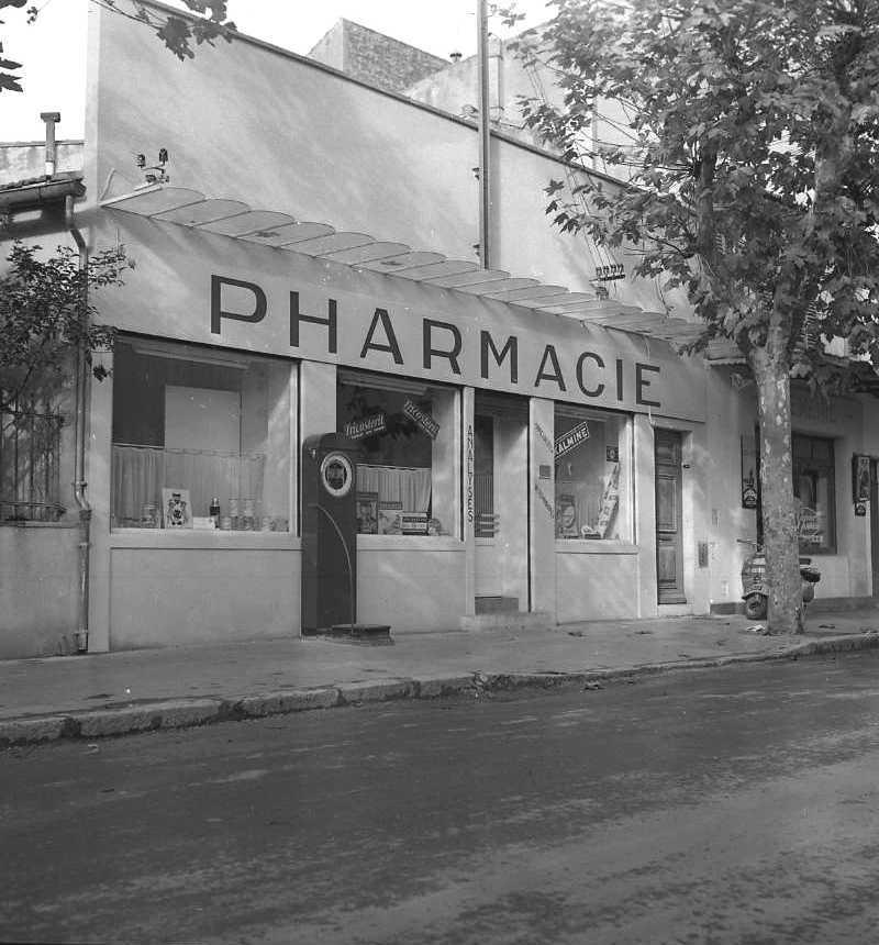 27Fi 3841 - La pharmacie Pracchia sur le boulevard de la République, faisant toujours face à l'école  Sainte Anne. A l'extérieur on y voit aussi le pèse-personne à 20 centimes qui distribuait des petits tickets avec le poids indiqué dessus. 27/11/1954