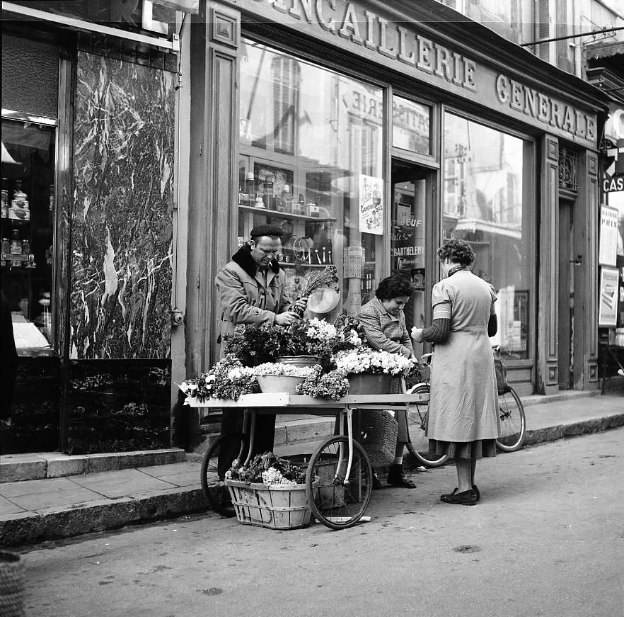 27Fi 2298 - Autre commerce ambulant, la marchande de fleurs et son charreton, rue François Donzel. 12/03/1955