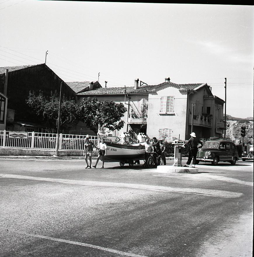27 Fi 1223 - 24.Déplacement insolite du bateau de pêche Le Colvert au carrefour du Vallat de Roubaud sous la bonne garde de l'agent de circulation. Serait-ce encore envisageable aujourd'hui ? - 16/09/1956