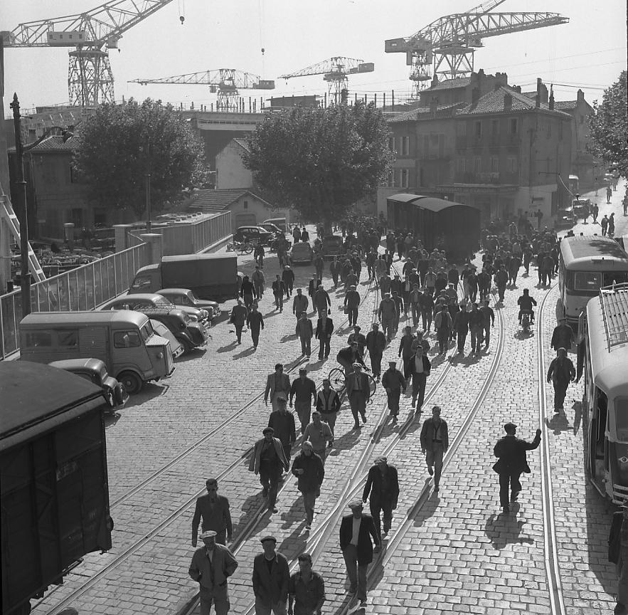 27 Fi 1317 - Sortie traditionnelle des ouvriers des CNC par la porte du bassin sur la place de l'Escalet. A droite on peut voir les cars de la CPTA garés devant la gare de l'Escalet, tandis que deux wagons stationnent en attendant d'être tractés par une l