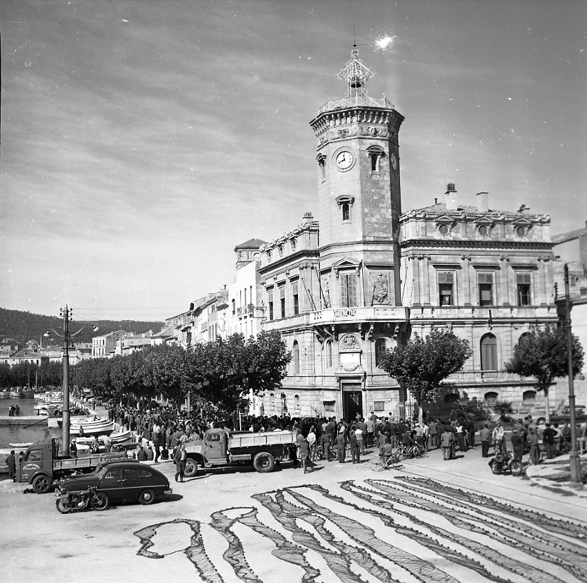 27 Fi 248 - Rassemblement devant le majestueux Hôtel de Ville. Au Premier plan, les filets des pêcheurs sèchent au soleil. 06/01/1955