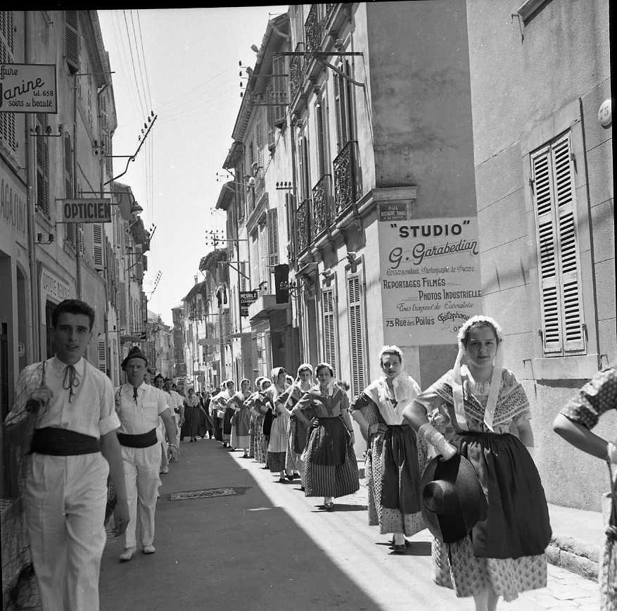27 Fi 2892 - Défilé de danseurs provençaux dans la rue des Poilus. Sur un des murs, on aperçoit la publicité du Studio Garabedian. 12/06/1955