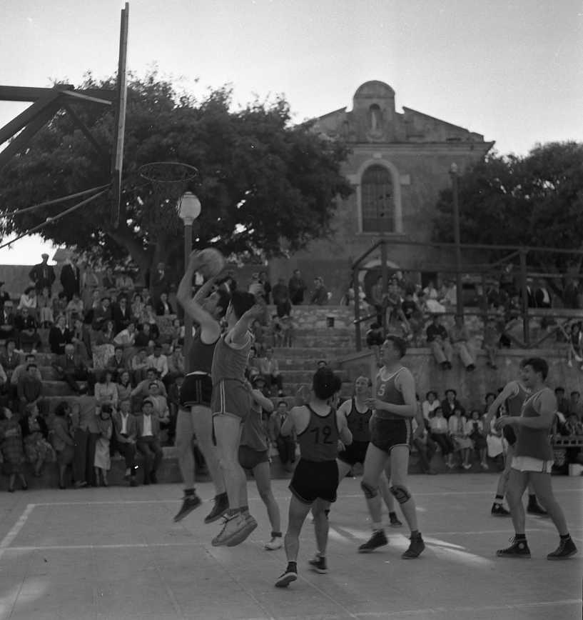 27 Fi 2915 - Action de match de basket sur l'esplanade du 8 mai1945 avec la chapelle des Pénitents Bleus en fond. 12/06/1955