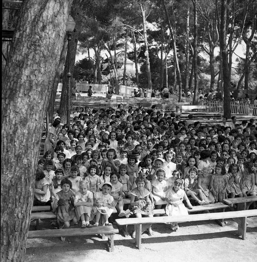 27 Fi 3112 - Remise de prix aux élèves au jardin de la Ville. Les fillettes attendent sagement à l'ombre des grands pins. 01/07/1955