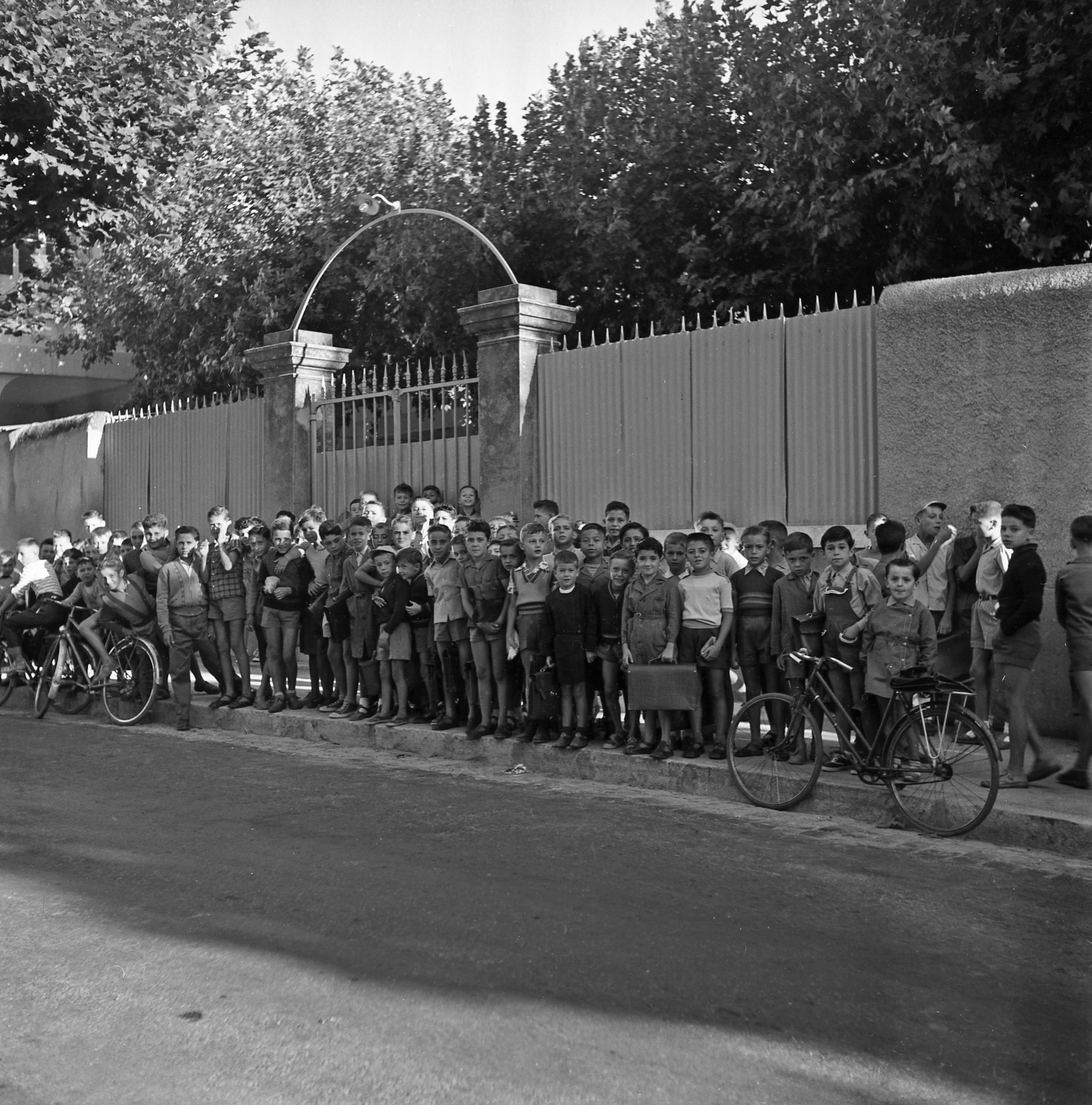 27 Fi 3286 Les garçons posant devant les grilles de l'école Jean Jaurès, le jour de la rentrée des classes. 17/09/1954