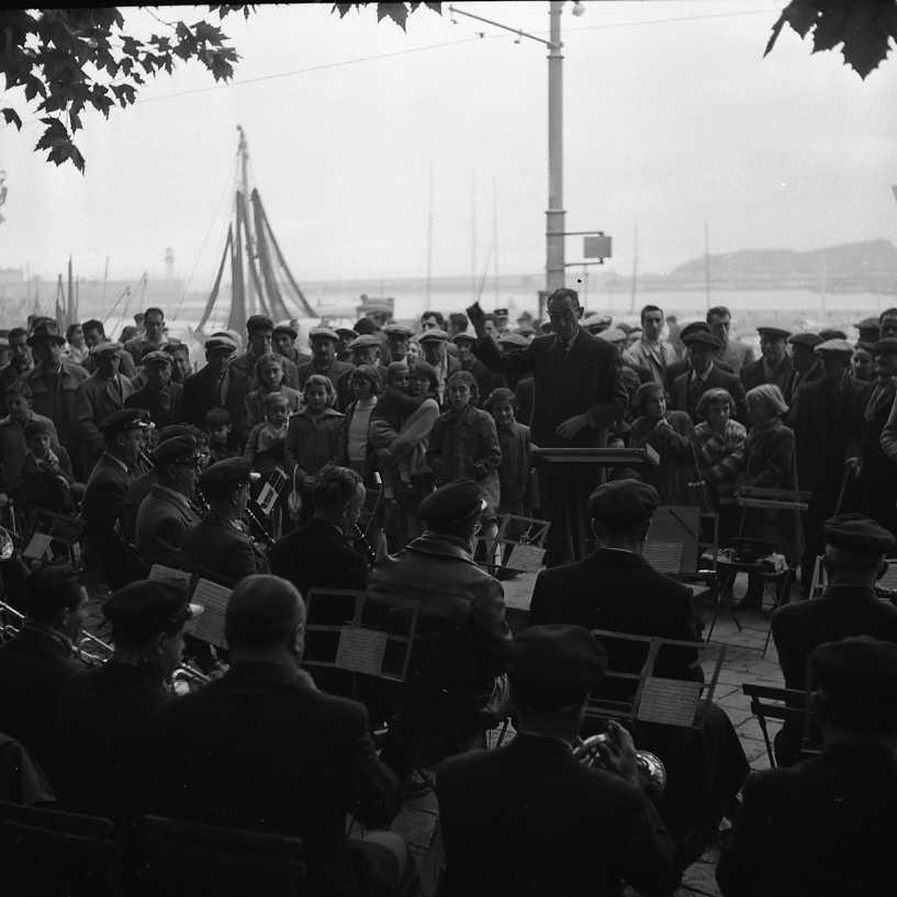 27 Fi 4128 - Les musiciens de l'orchestre municipal attentifs aux directives de leur « chef », Antoine Masson,  lors d'une représentation sur le port. 27/11/1955
