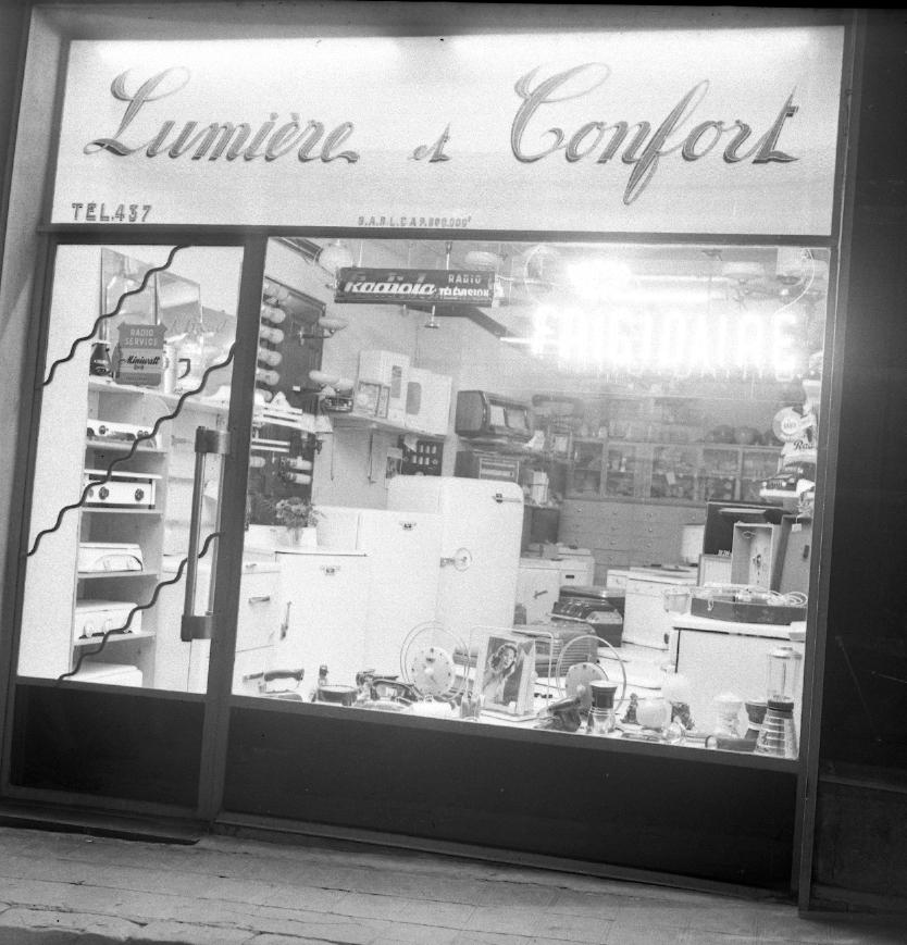 27Fi 2408 - La vitrine moderne et  illuminée du magasin « Lumière et Confort » qui se trouvait en haut de la rue des Poilus. 2/04/1955