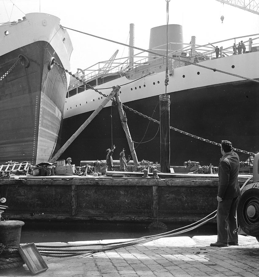 27Fi 2401 Un ponton amène les équipements d'armement, qui seront embarqués à bord des navires en cours de finition à quai. 2/04/1955