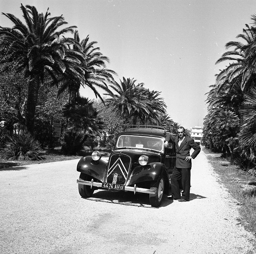 27Fi 2477 - Le taxi Loulou pose fièrement devant son automobile dans l'allée Lumière. Derrière, on aperçoit le palais Lumière, ancienne résidence estivale des deux inventeurs du Cinéma et de leur famille. 14/04/1955