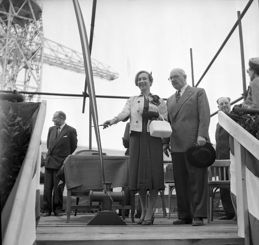 27Fi 1004 Jour de lancement du Ninive. En présence du PDG des CNC, Jean-Marie TERRIN ; la Marraine, Madame CALVET s'apprête à couper le ruban, libérant ainsi la traditionnelle bouteille de champagne. 4/06/1955