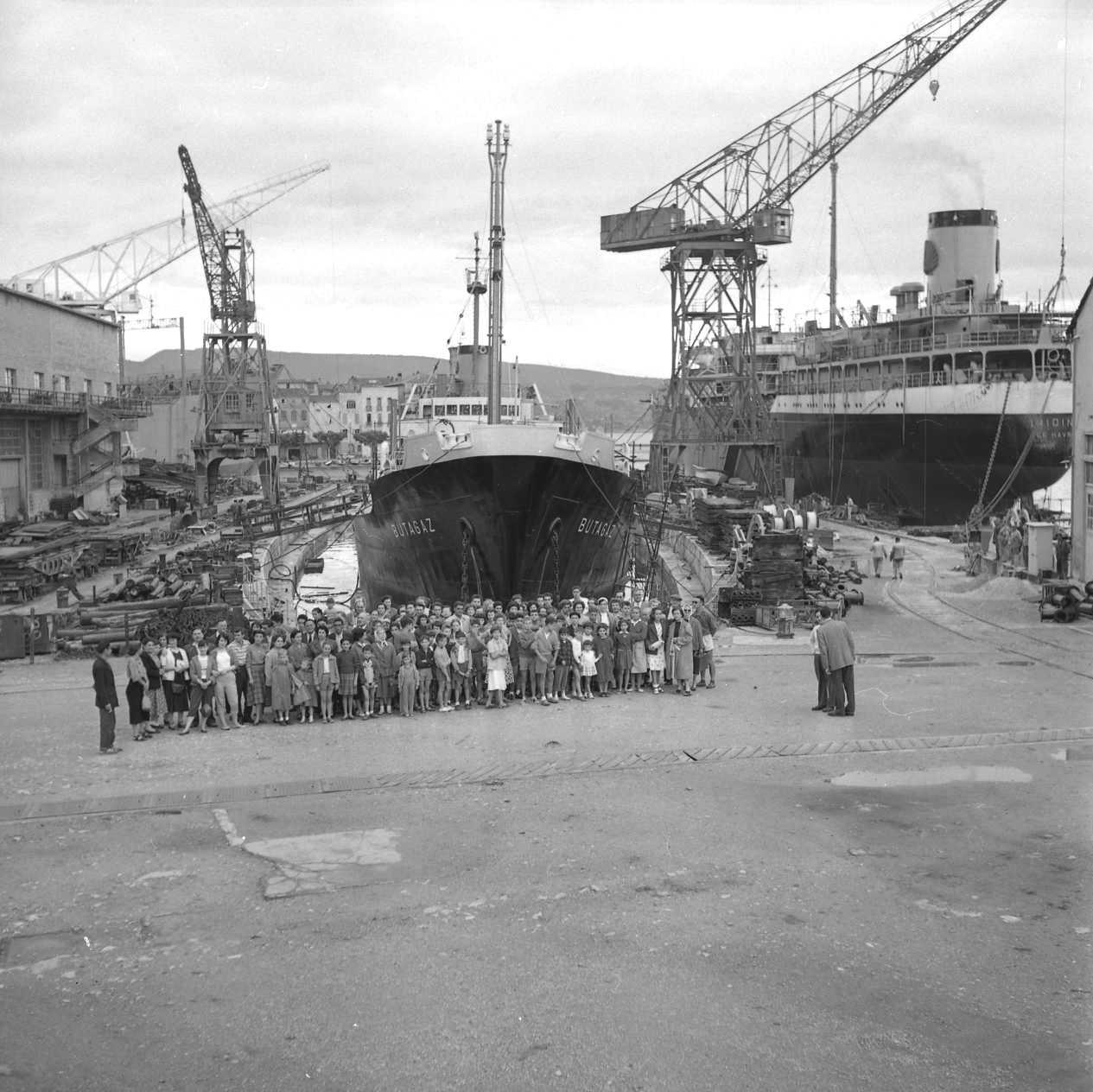 27Fi 2949 Les colons du club Léo Lagrange en visite dans les chantiers, devant le Butagaz (1er transport de gaz construit aux CNC) dans le bassin de radoub. 19/06/1955