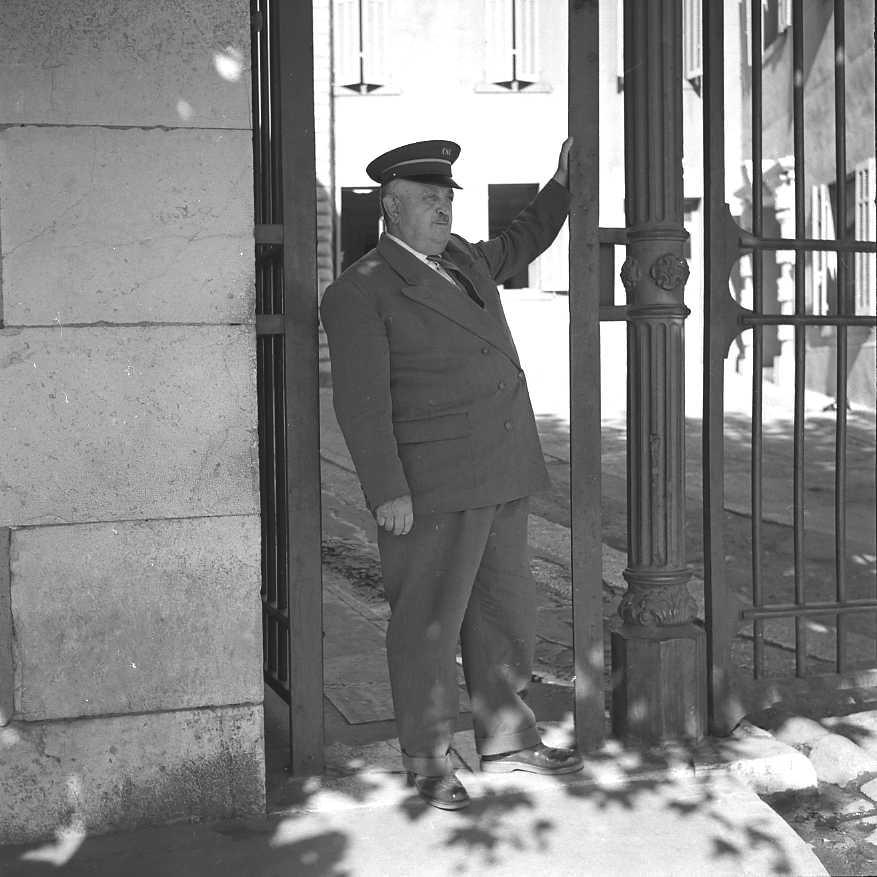 27Fi 4007 Mr Curinier, gardien des CNC, officiant devant les grilles d'entrée de la direction. 20/09/1955