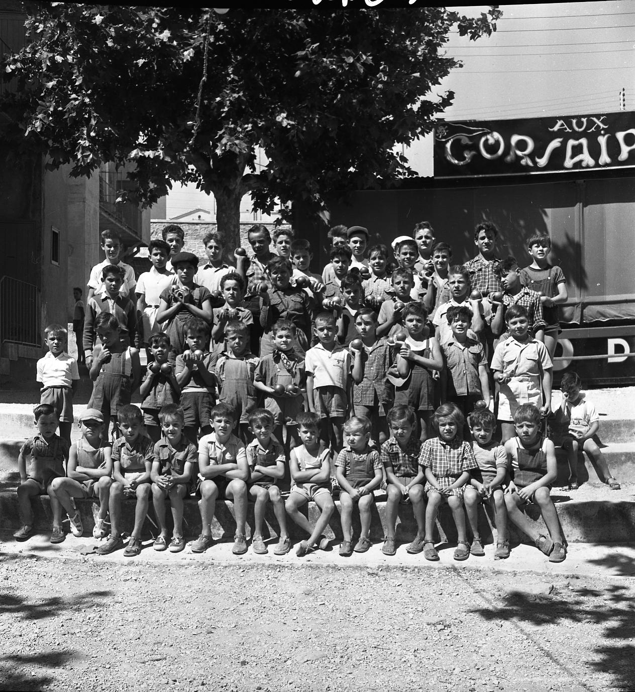 42Fi 0132 « Ces champions de boules en herbe prennent leur rôle au sérieux. » (Le Provençal). Il s'agit du concours de boules de la St Victor. Tous les petits de la Cité y participent. 19/07/1953