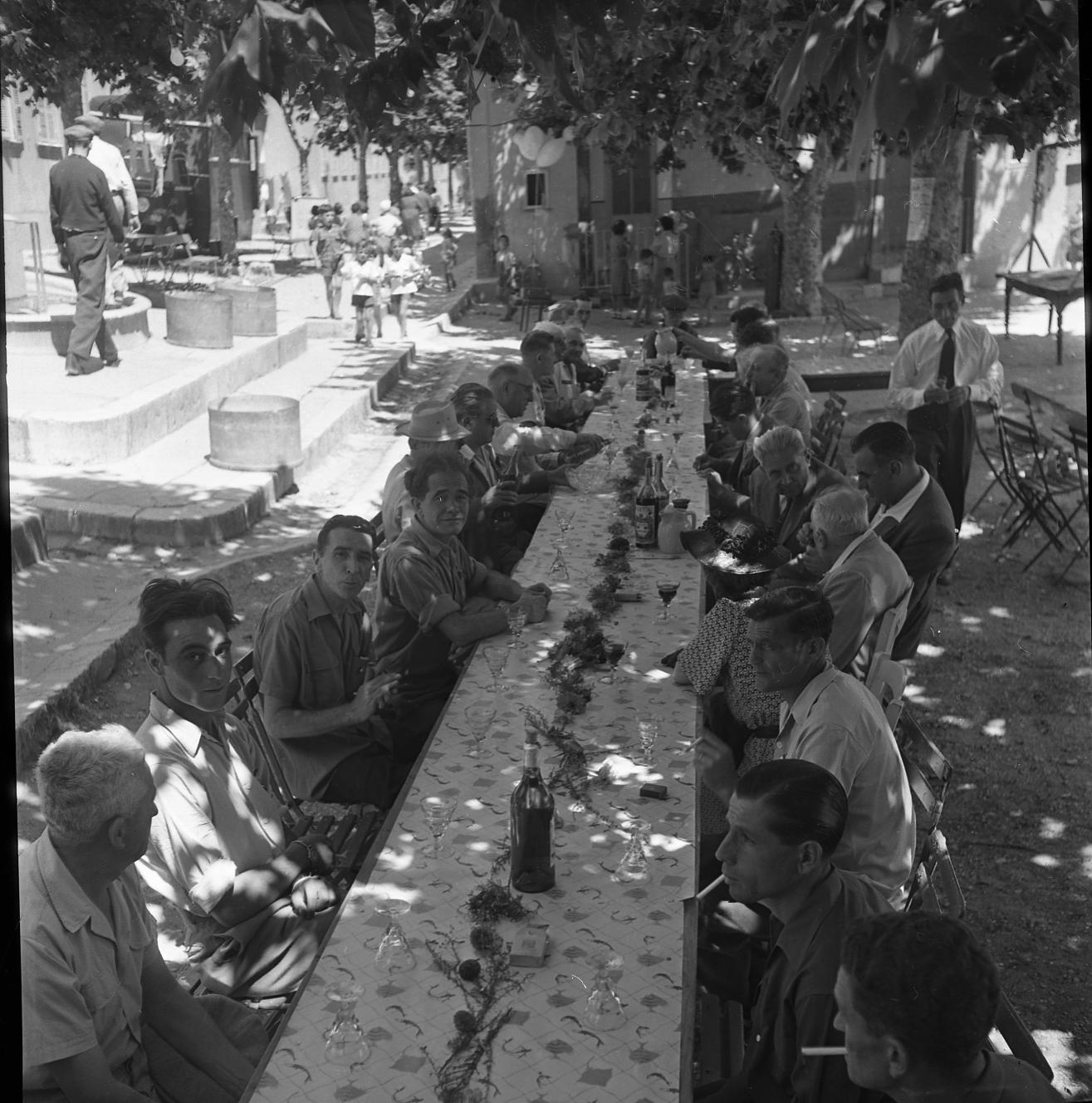 42Fi 0135 Lors de la St Victor, belle tablée qui regroupe les organisateurs de cette grande fête de la cité ouvrière. Parmi les invités d'honneur, le maire Jean Graille et le baron de Vaux, descendant de Victor Delacour. 19/07/1953