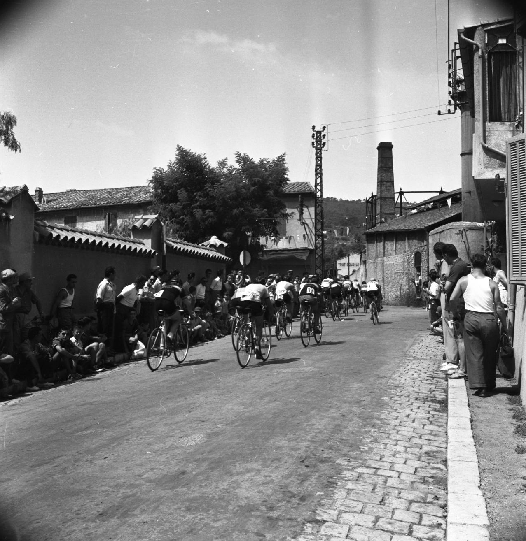 42Fi 0252 Course cycliste sur l'avenue Gallieni pour la fête de la Ste Marthe, on distingue en fond la cheminée de l'ancienne usine à gaz. 26/07/1953