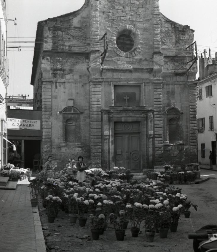 42Fi 1239 Vente de chrysanthèmes sur la place Esquiros en prévision du 1er novembre. La façade de la chapelle est bien vieillissante. 27/10/1953