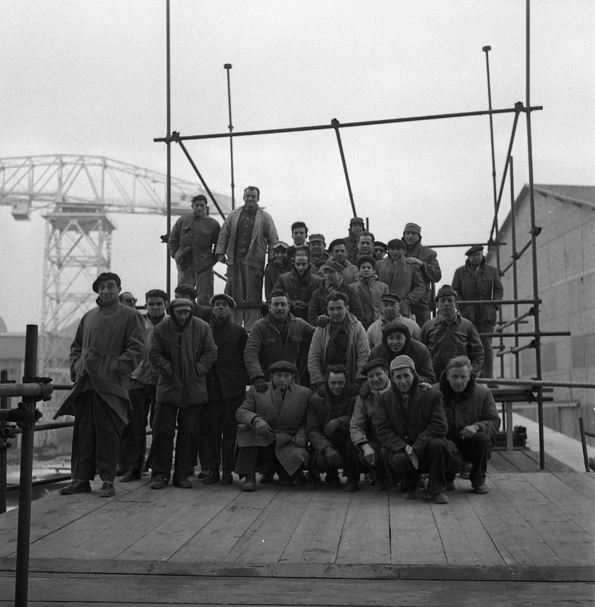 46 Fi 003 - En tête de cale, les ouvriers du Sindh prennent la pose sur les échafaudages juste avant le lancement du navire et savourent le résultat de leur travail. - 11/02/1956