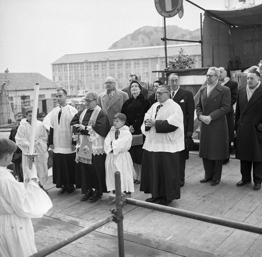 46 Fi 026 - Moment solennel, le prêtre entouré de ses enfants de chœur, procède à la bénédiction du navire sous le regard admiratif de la marraine. - 11/02/1956