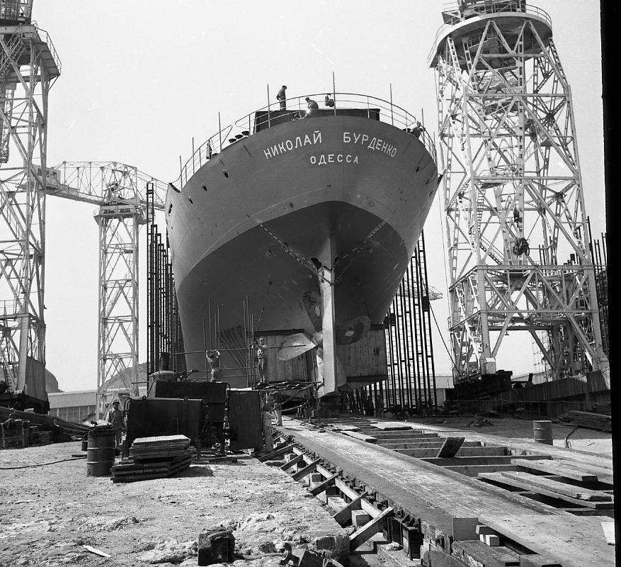 46 Fi 0267 - Vue imprenable de l'arrière du cargo Nikolay Burdenko et de son hélice. Les ouvriers achèvent le démontage des échafaudages afin de préparer le lancement. On distingue au premier plan les caisses à suif. - 4/05/1956