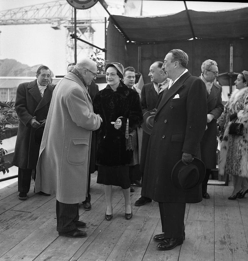 46 Fi 035 - Poignée de main accueillante de Jean-Marie Terrin, Président Directeur Général des CNC, à la marraine du cargo Sindh, Madame Tron, sous l'œil bienveillant de son frère Augustin Terrin. - 11/02/1956