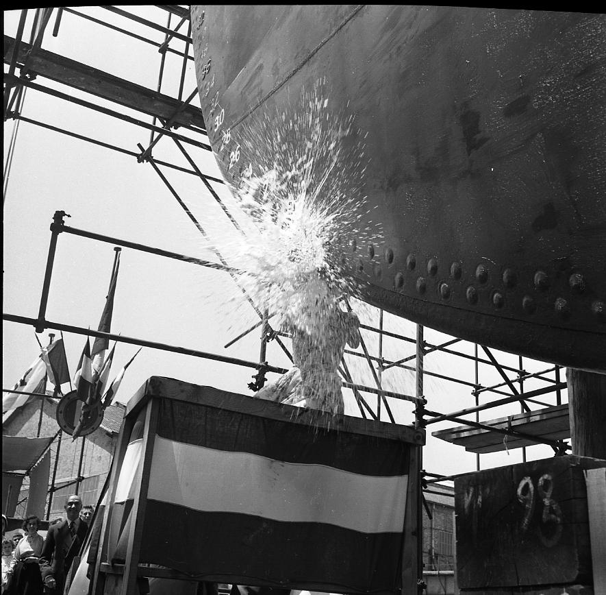 46 Fi 0410 - D'un geste hésitant, l'élégante marraine du Tigre, Madame Poirier, s'apprête à casser la bouteille. L'étrave du navire mélange encore rivetage et soudure ! - 23/06/1956