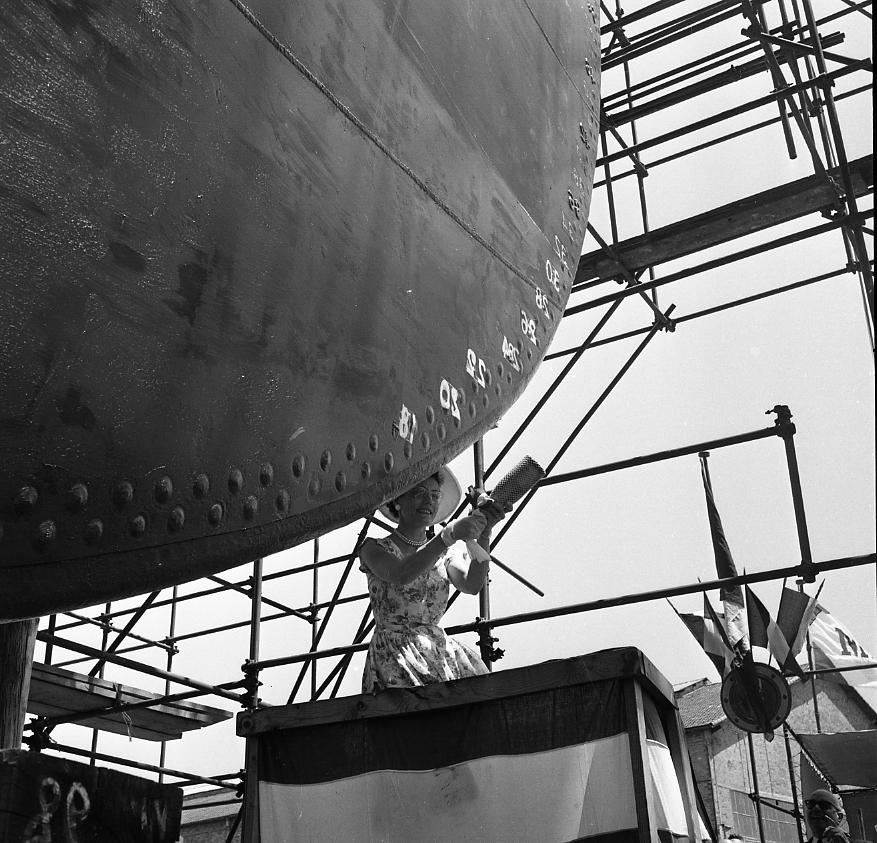 46 Fi 0415 - D'un geste hésitant, l'élégante marraine du Tigre, Madame Poirier, s'apprête à casser la bouteille. L'étrave du navire mélange encore rivetage et soudure ! - 23/06/1956